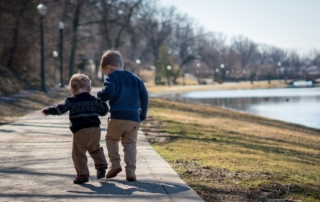 two young brothers walking together down a sidewalk-kindness