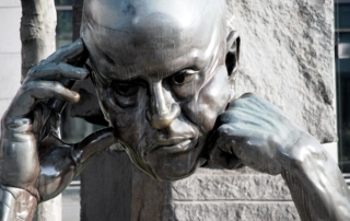 sculpture of a man's head held by his two hands-cause and effect
