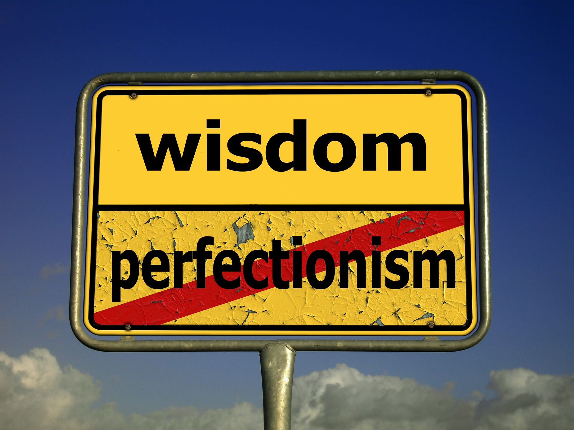 yellow road sign with the word wisdom and below it the word perfectionism marked out with a red line-perfect is the enemy