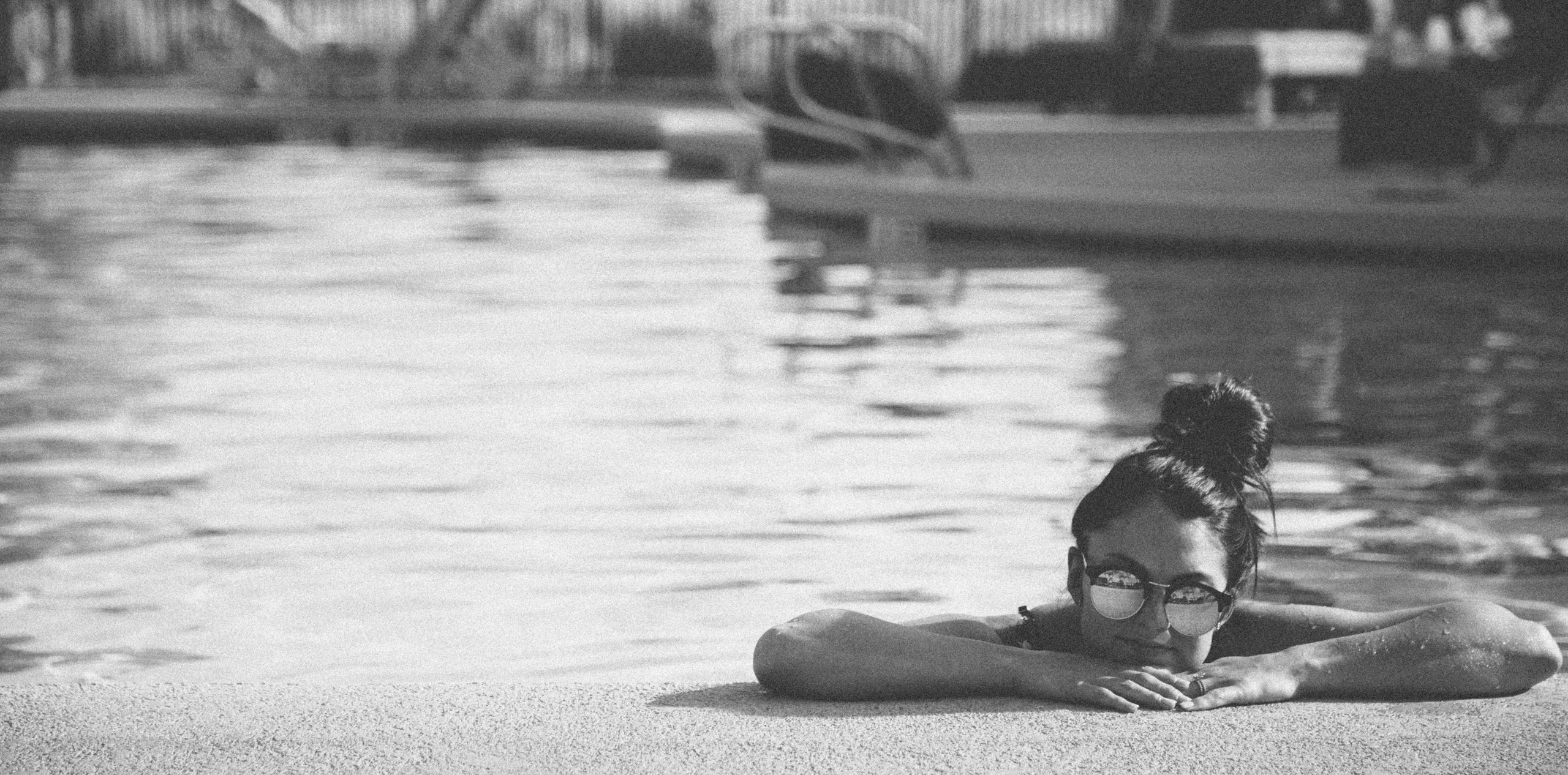 girl looking over the edge of a pool wearing sunglasses-live life to the fullest