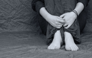 black and white photo of a person sitting only showing their crossed hands and bare feet signifying the invisibility of the victims of human trafficking