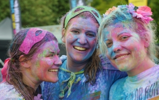 three girls with different colors of paint on their faces , in their hair, and on their clothes-humor