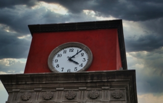 A clock on the red parapet of a building with stormy clouds in the sky-what's in a day?